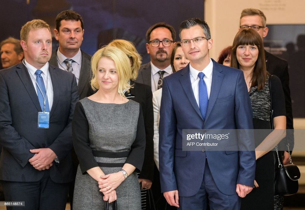 Slovenian presidential candidate and Mayor of Kamnik Marjan Sarec (2R) and his wife Barbara (C/L) arrive to address media representatives after the first official results of presidential elections were released in Ljubljana on October 22, 2017.