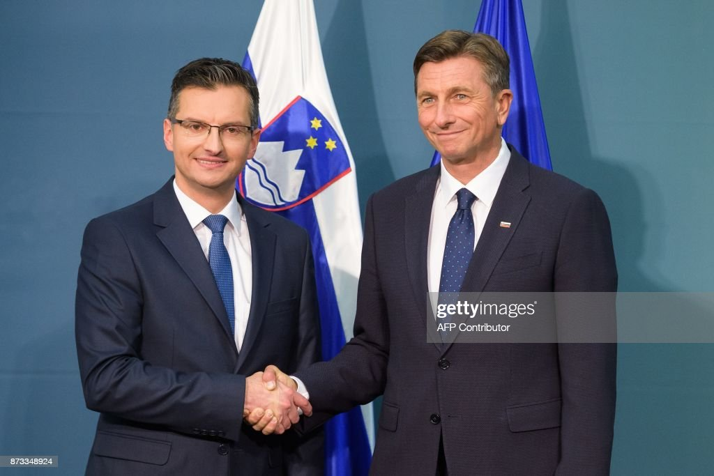 Slovenian presidential candidate and Mayor of Kamnik Marjan Sarec (L) and re-elected Slovenian President Borut Pahor shake hands after the release of the first results of the second round of the presidential elections in Ljubljana on November 12, 2017. Slovenia's internet-savvy President Borut Pahor on November 12 won a second term in a runoff vote that was marred by an abysmally low turnout. / AFP PHOTO / Jure Makovec