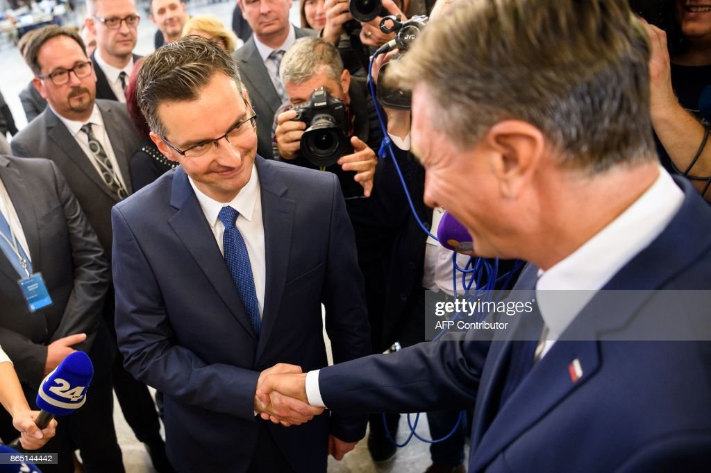 Slovenian presidential candidate and Mayor of Kamnik Marjan Sarec (L) shakes hands with fellow candidate and current President of Slovenia Borut Pahor after the first official results of presidential elections were released in Ljubljana on October 22, 2017.