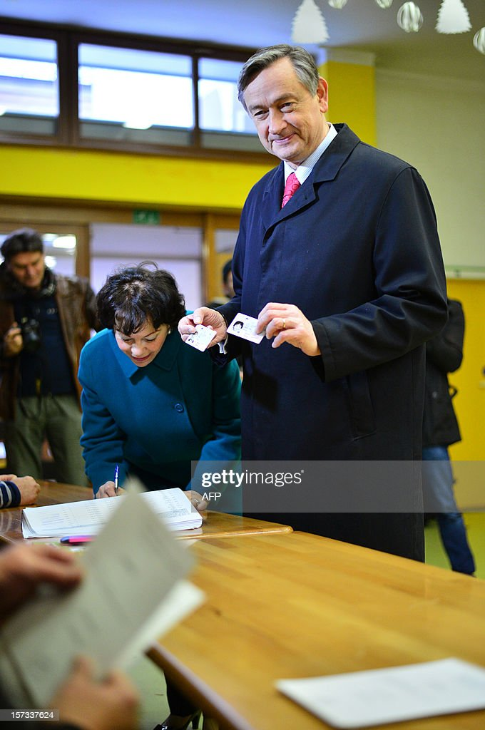 Slovenian Presidential candidate Danilo Turk (R) shows his identity card before casting his ballot at a polling station in Ljubljana, Slovenia, on December 2, 2012. Slovenians started voting today in a presidential run-off with polls favouring former prime minister Borut Pahor, despite his promise to help an increasingly unpopular centre-right government lead the eurozone country out of the crisis. AFP PHOTO / Jure Makovec