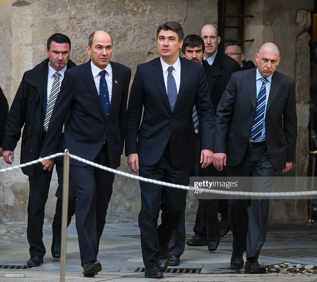 Slovenian Prime Minister Janez Jansa (2L) and his Croatian counterpart Zoran Milanovic (C) shake hands as they arrive for a meeting in Mokrice on March 11, 2013 in a bid to end a banking dispute which has threatened Croatia's entry into the EU this July.