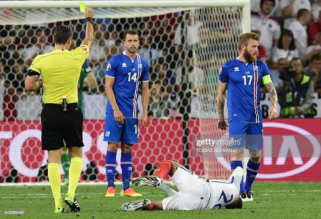 Slovenian referee Damir Skomina gives a yelow card against Iceland's midfielder Aron Gunnarsson (R) as Iceland's defender Kari Arnason (C) looks on during Euro 2016 round of 16 football match between England and Iceland at the Allianz Riviera stadium in Nice on June 27, 2016. / AFP / TOBIAS