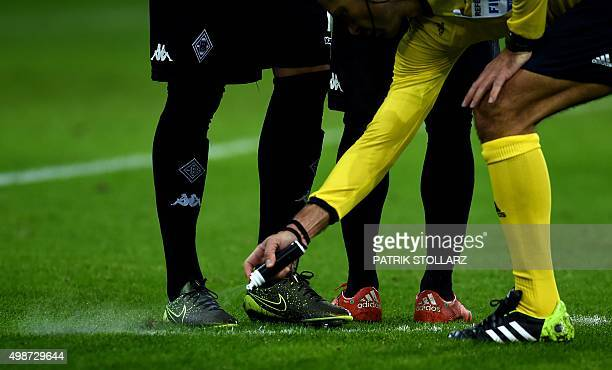 Slovenian referee Damir Skomina marks a freekick point with a marker spray during the Group D secondleg UEFA Champions League football match Borussia...