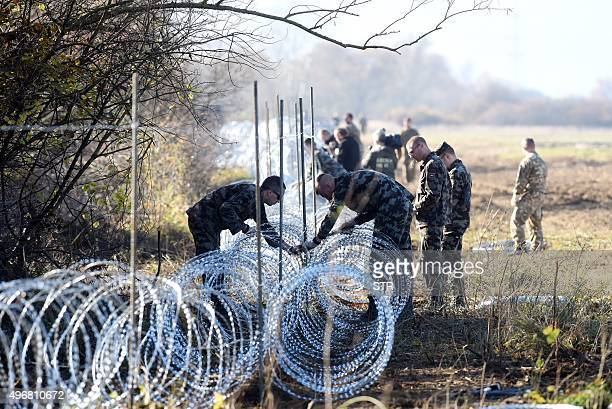 Slovenian soldiers set barbed wire fences on the SlovenianCroatian border near Rakovec on November 12 2015 Slovenia found itself on the Balkans route...
