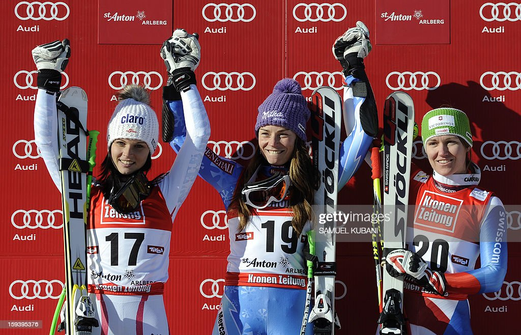 Slovenian Tina Maze (C) celebrates on podium her first place with second placed Austrian Anna Fenninger (L) and third placed Fabienne Suter of Switzerland (R) at the women's World Cup Super G, on January 13, 2013 in St Anton am Arlberg, Austria. AFP PHOTO / SAMUEL KUBANI