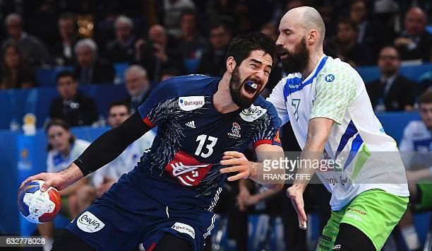 TOPSHOT Slovenia's back Vid Kavticnik holds back France's centre back Nikola Karabatic during the 25th IHF Men's World Championship 2017 semifinal...