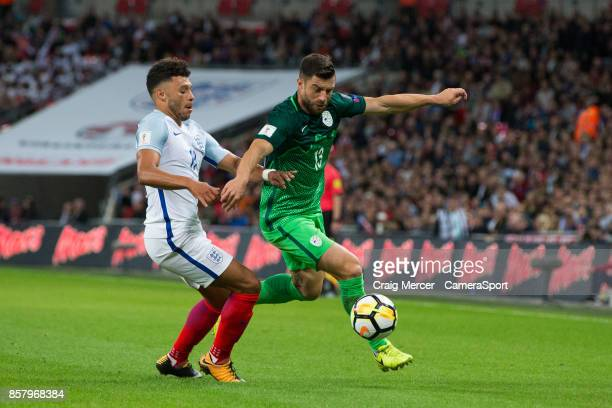 Slovenia's Bojan Jokic vies for possession with England's Alex OxladeChamberlain during the FIFA 2018 World Cup Qualifier between England and...