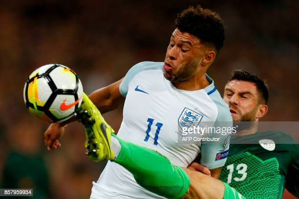 TOPSHOT Slovenia's defender Bojan Jokic challenges England's midfielder Alex OxladeChamberlain during the FIFA World Cup 2018 qualification football...