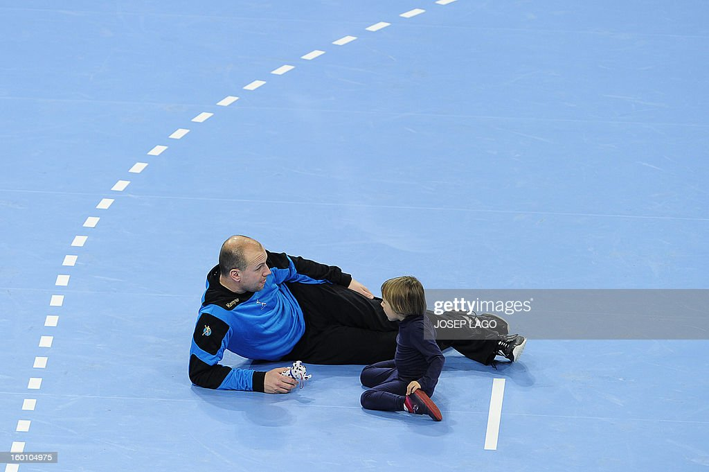 Slovenia's goalkeeper Gorazd Skof plays with his child at the end of the 23rd Men's Handball World Championships bronze medal match Slovenia vs Croatia at the Palau Sant Jordi in Barcelona on January 26, 2013. AFP PHOTO/ JOSEP LAGO