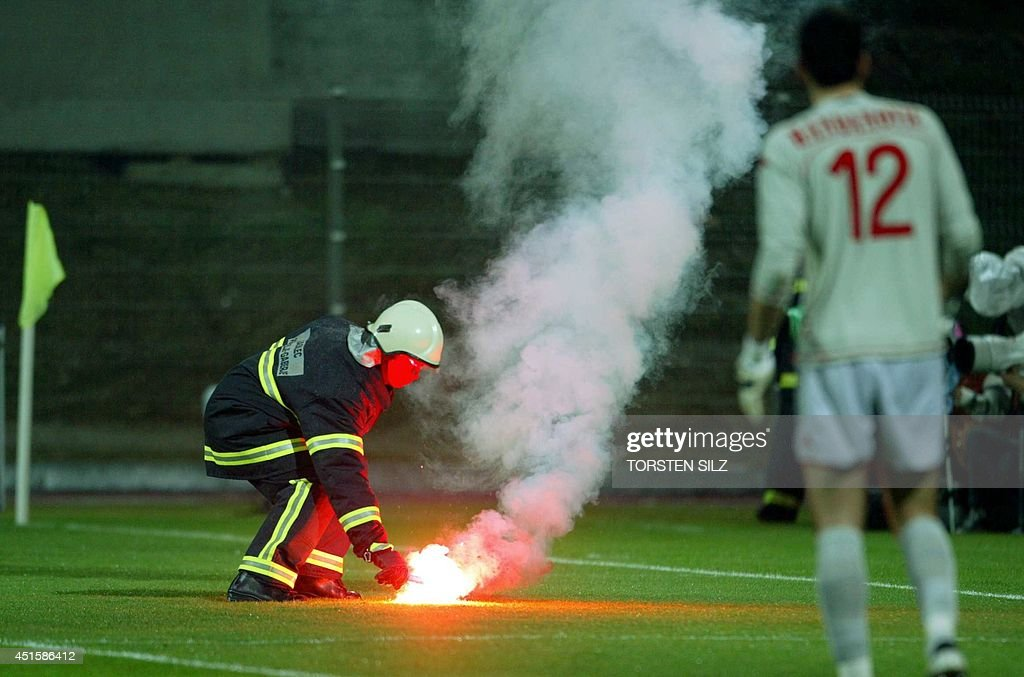Slovenia's goalkeeper Samir Handanovic looks on as a firemen removes a firework from the field during the friendly football match of Slovenia against...
