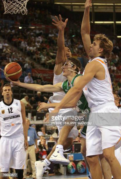 Slovenia's Goran Dragic vies with Germany's Ademola Okulaja and Dirk Nowitzki during a qualifying round Group F of the European Basketball...