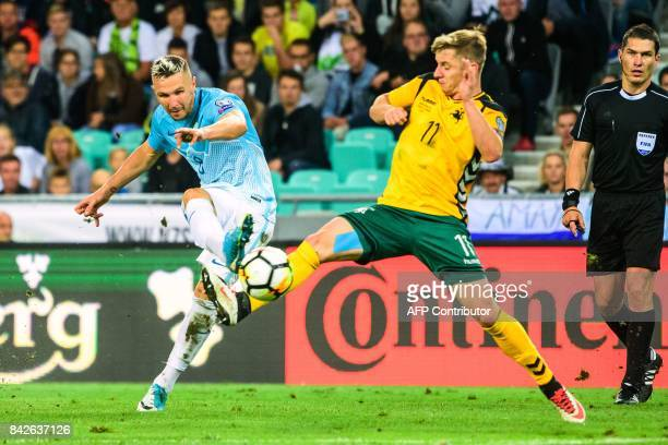 Slovenia's Jasmin Kurtic vies with Lithuania's Arvydas Novikovas during the FIFA World Cup 2018 qualification football match between Slovenia and...