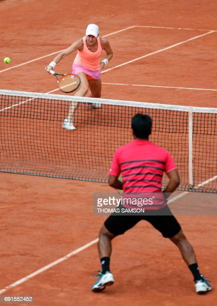 Slovenia's Katarina Srebotnik and South Africa's Raven Klassen return the ball to Switzerland's Martina Hingis and India's Leander Paes during their...