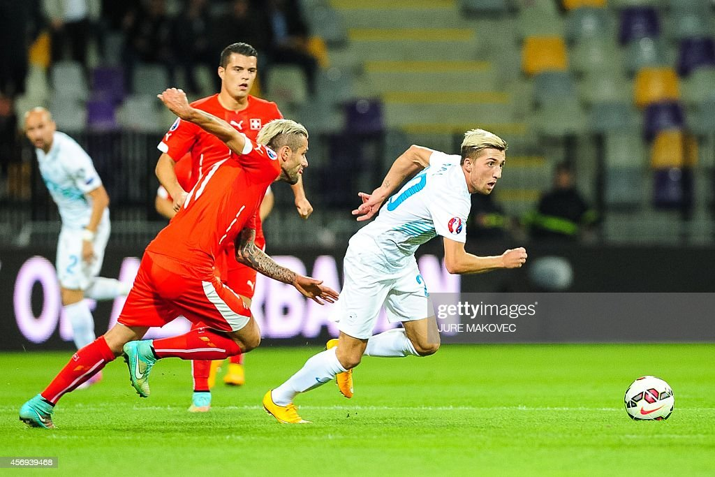 Slovenia's Kevin Kampl fights for the ball with Switzerland's Valon Behrami on October 9 2014 during a Euro 2016 qualifying match Slovenia vs...