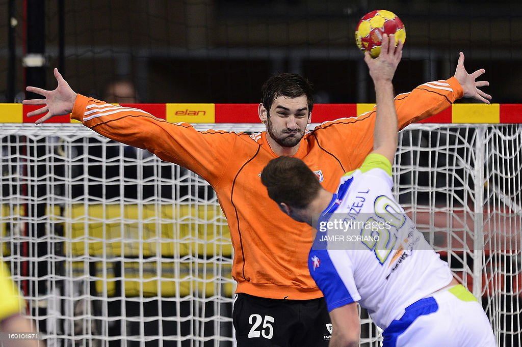 Slovenia's left wing Luka Zvizej (R) shoots to score past Croatia's goalkeeper Mirko Alilovic during the 23rd Men's Handball World Championships bronze medal match Slovenia vs Croatia at the Palau Sant Jordi in Barcelona on January 26, 2013.