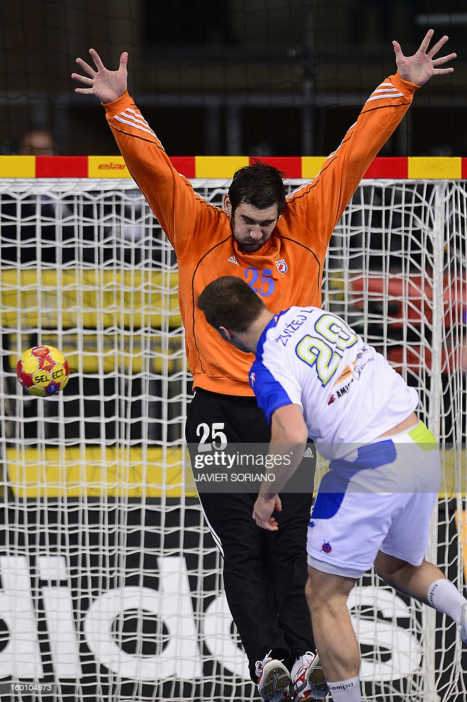 Slovenia's left wing Luka Zvizej (R) shoots to score past Croatia's goalkeeper Mirko Alilovic during the 23rd Men's Handball World Championships bronze medal match Slovenia vs Croatia at the Palau Sant Jordi in Barcelona on January 26, 2013. AFP PHOTO/ JAVIER SORIANO