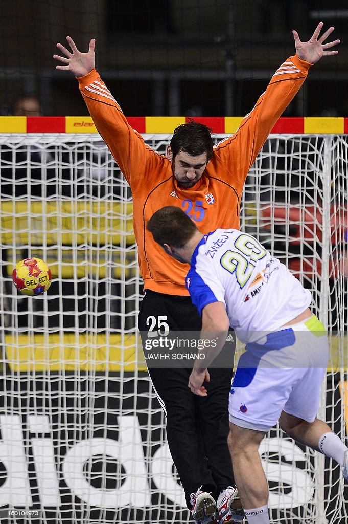 Slovenia's left wing Luka Zvizej (R) shoots to score past Croatia's goalkeeper Mirko Alilovic during the 23rd Men's Handball World Championships bronze medal match Slovenia vs Croatia at the Palau Sant Jordi in Barcelona on January 26, 2013.
