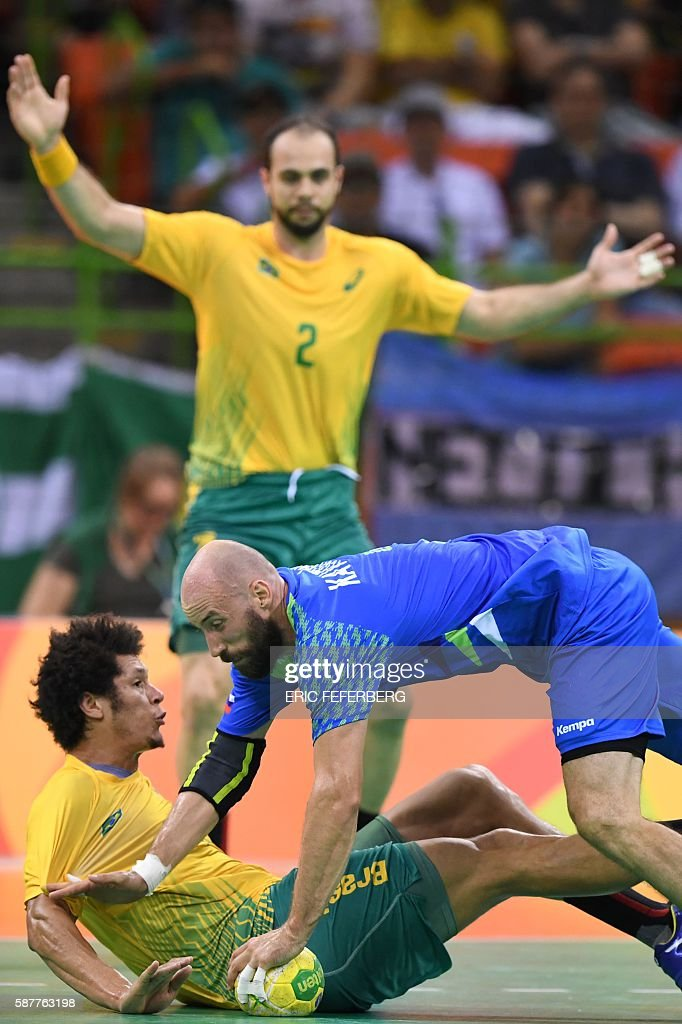 Slovenia's right back Vid Kavticnik and Brazil's left wing Thiagus dos Santos fall past Brazil's centre back Henrique Teixeira during the men's...