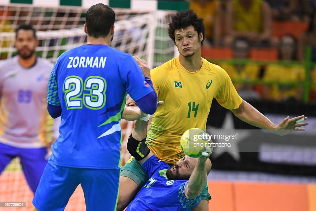 Slovenia's right back Vid Kavticnik is fouled by Brazil's left wing Thiagus dos Santos during the men's preliminaries Group A handball match Brazil...