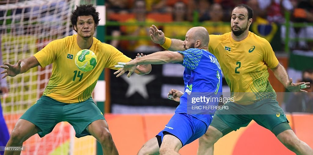 Slovenia's right back Vid Kavticnik shoots past 14 and Brazil's centre back Henrique Teixeira during the men's preliminaries Group A handball match...