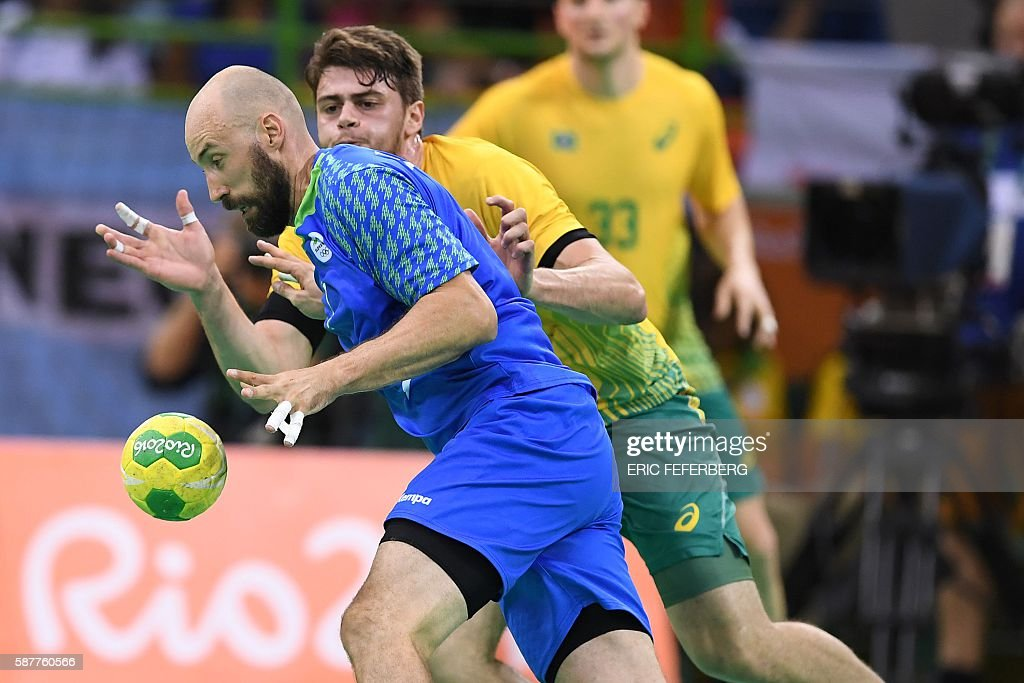 Slovenia's right back Vid Kavticnik vies with Brazil's left back Haniel Langaro during the men's preliminaries Group A handball match Brazil vs...