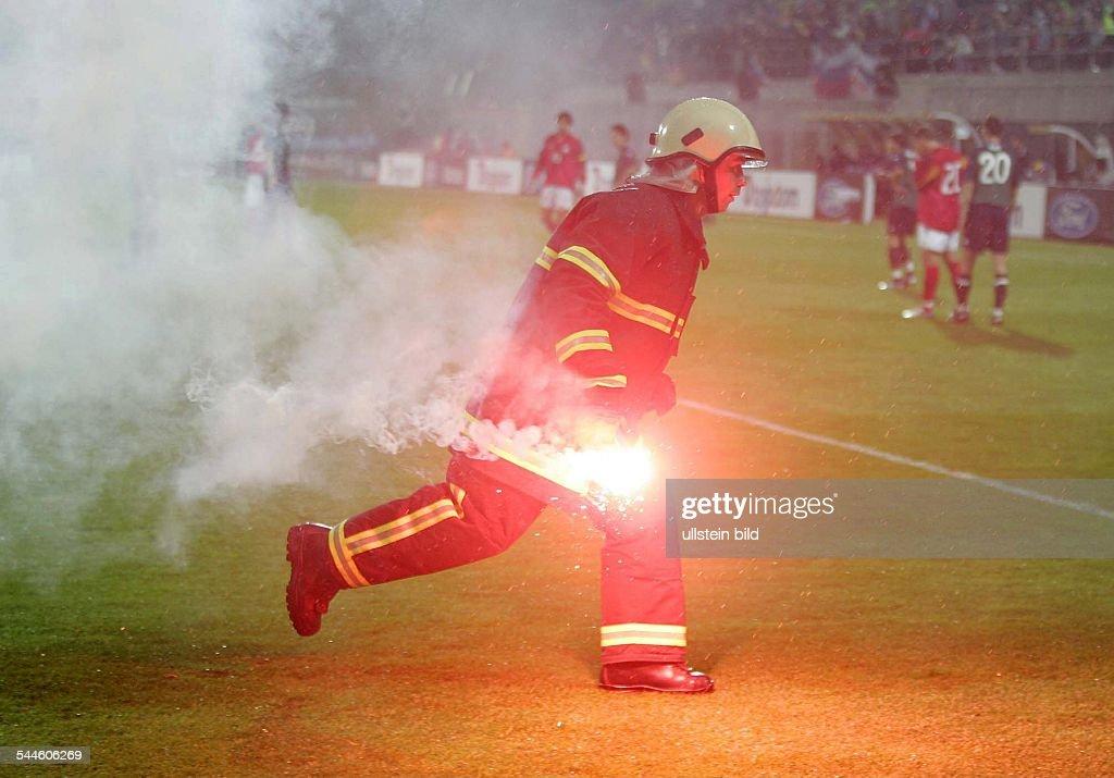 Slowenien Celje Feuerwehrmann raeumt ein bengalisches Feuer vom Spielfeld beim FussballLaenderspiel gegen Deutschland