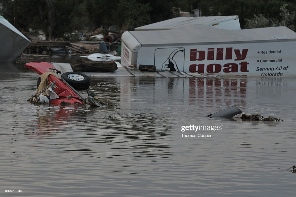 Slowly receding water around submerged cars and trucks at a salvage yard is shown September 17, 2013 near Evans, Colorado. Even as flooding subsides, many in the hardest hit areas of the state remain stranded by washed out roads and rushing creeks and without water and power.
