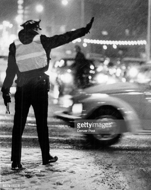 Slowmoving motorist at 15th and California Sts is directed through the flakes during Monday evening rush hour Credit Denver Post