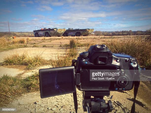 Slr Camera In Front Of Armored Vehicles On Field Against Sky