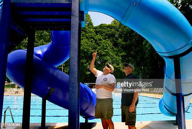 PoolsA Brian Price/For Fairfax County Times Tom Bruno and Chris Kirkman work on finishing the installation of a new water slide May 21 at the Orange...