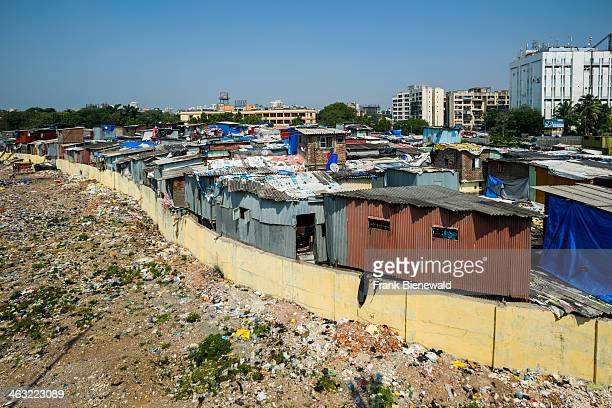 A slum area behind a wall and with new buildings in the distance