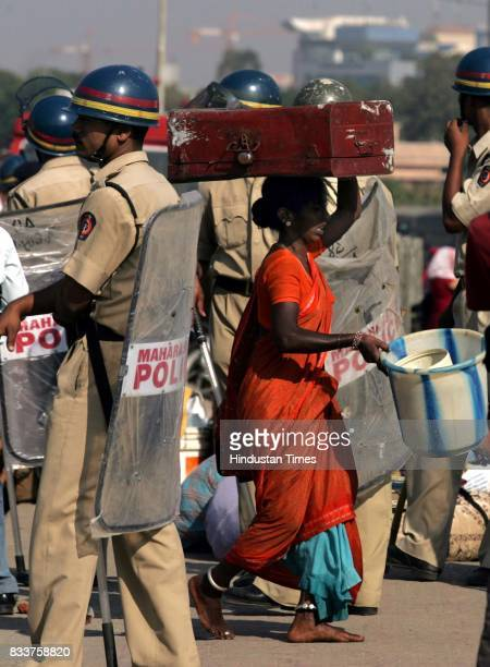 A woman moves out of the illegal hutments at encroached area of University campus at Bandra Kurla Complex after municipal authorities started...
