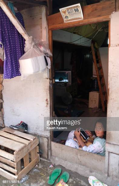A slum dweller girl seen sat on the ground inside a makeshift home with an iPad on her lap in the old town on November 27 2016 in Jakarta Indonesia