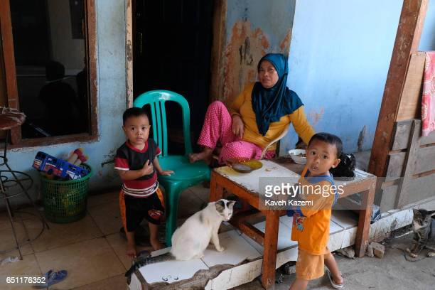 A slum dweller mother in veil and her sons seen with their two cats outside their shanty house in old town on November 27 2016 in Jakarta Indonesia