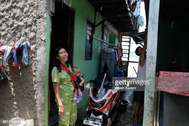 A slum dweller mother with her baby and husband in the background seen outside their makeshift house in the old town on November 27 2016 in Jakarta...