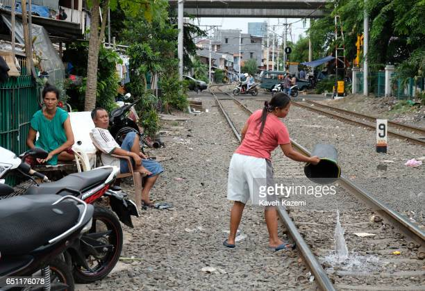 A slum dweller woman empties a bucket of waste water on the rairoad track outside her makeshift house in Kota City on November 25 2016 in Jakarta...