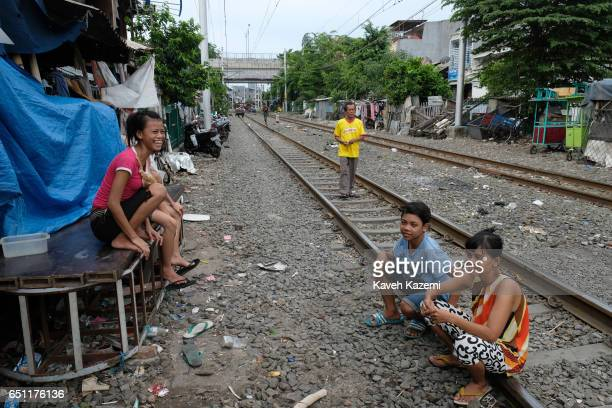 Slum dwellers hang around outside their huts by the rairoad track in Kota City on November 25 2016 in Jakarta Indonesia The slum dwellers have been...