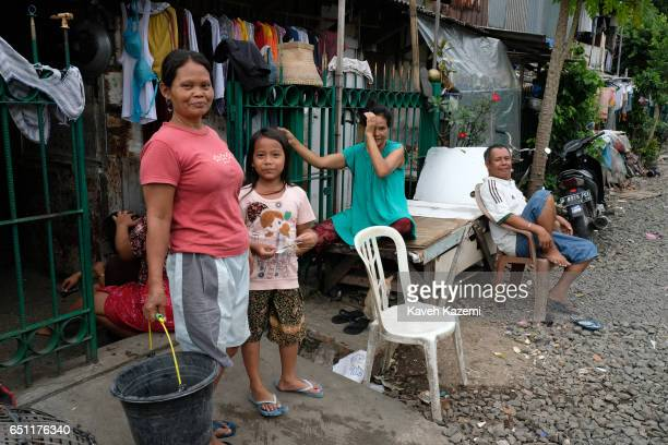Slum dwellers hang around outside their makeshift houses by the rairoad track in Kota City on November 25 2016 in Jakarta Indonesia The slum dwellers...