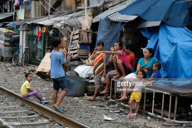 Slum dwellers hang around outside their shanty houses by the rairoad track in Kota City on November 25 2016 in Jakarta Indonesia The slum dwellers...