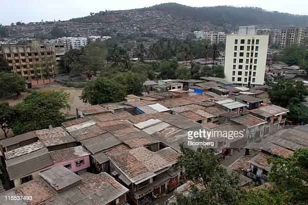 Slum dwellings with asbestos rooftops stand next to residential buildings in Mumbai India on Tuesday May 17 2011 India ranks as the world's largest...