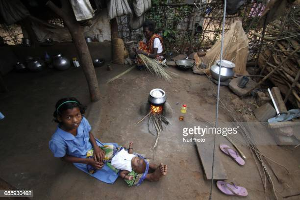 A slum girl plays with her little brother as she sits near to a traditional cooking vat at a slum in Bhubaneswar on March 21 2017