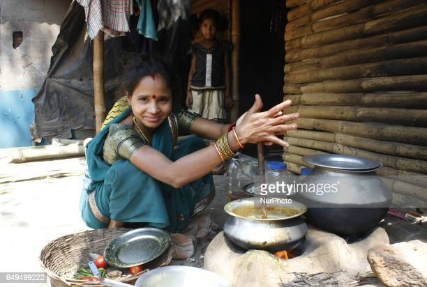 A slum living woman is making foods for the members of her family outside of their makeshift on the International Womens Day in the eastern Indian...