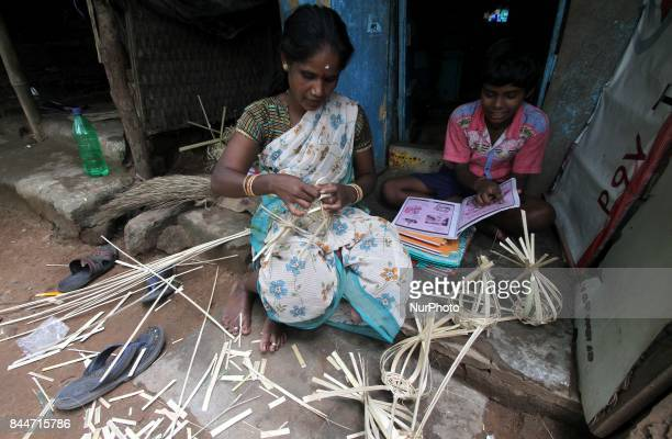 A slum living woman prepares fancy bamboo baskets ahead of the festivities session begins and sale it at that time near by goddess worship venues in...