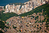 Aerial view of Favela da Rocinha, Biggest Slum in Brazil on the Mountain in Rio de Janeiro, and Skyline of the City behind.