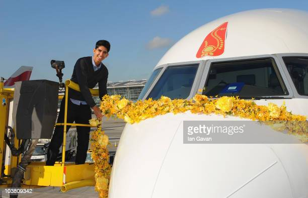 Slumdog Millionaire actor Dev Patel places a giant traditional Indian Bindi and garland on the nose of the new British Airways Boeing 777 300ER on...