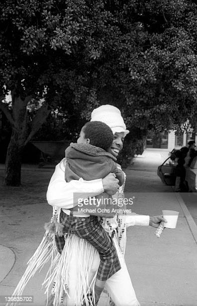 Sly Stone of the psychedelic soul group 'Sly and the Family Stone' carries a child on the Warner Brothers lot in circa 1970 in Los Angeles California
