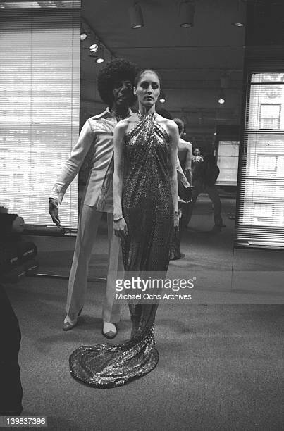 Sly Stone of the psychedelic soul group 'Sly And The Family Stone' in fashion designer Halston's studio standing behind a model wearing his future...