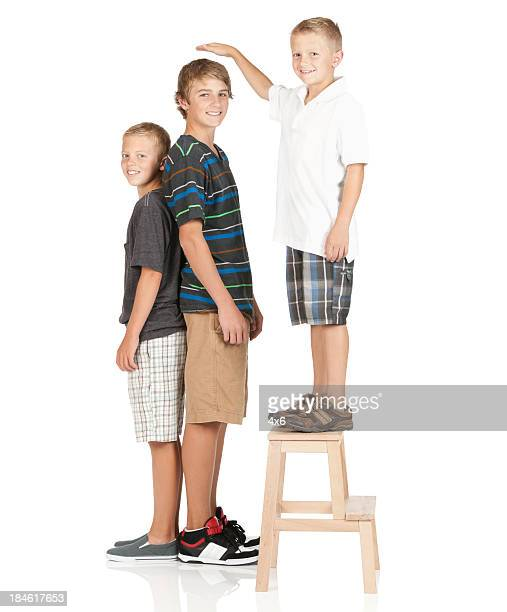 Smal boy standing on stool and comparing height