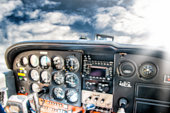 Vibrant color photography of small tourism airplane cockpit interior totally defocused and blurred, with basic common and pretty old control instrument panel. Image taken flying without people, in mid