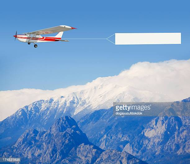 A small airplane towing a banner over a mountain landscape